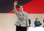 Newly elected CDU chairwoman Annegret Kramp-Karrenbauer, left, waves during the party convention of the Christian Democratic Party CDU in Hamburg, Germany, Friday, Dec. 7, 2018, after German Chancellor Angela Merkel didn't run again for party chairmanship after more than 18 years at the helm of the party. (AP Photo/Michael Sohn)