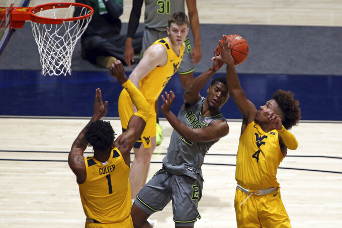 Baylor guard Jared Butler (12) is defended by West Virginia guard Miles McBride (4) and forward Derek Culver (1) during overtime in an NCAA college basketball game Tuesday, March 2, 2021, in Morgantown, W.Va. (AP Photo/Kathleen Batten)