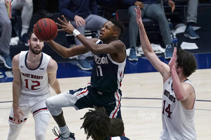 Gonzaga guard Joel Ayayi, middle, shoots between Saint Mary's guard Tommy Kuhse (12) and forward Kyle Bowen (14) during the first half of an NCAA college basketball game in Moraga, Calif., Saturday, Jan. 16, 2021. (AP Photo/Jeff Chiu)