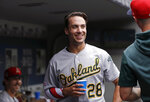 Oakland Athletics' Matt Olson, right, smiles in the dugout after his three-run home run against the Seattle Mariners as starting pitcher Daniel Mengden looks on from the bench behind in the first inning of a baseball game Sunday, July 7, 2019, in Seattle. (AP Photo/Elaine Thompson)