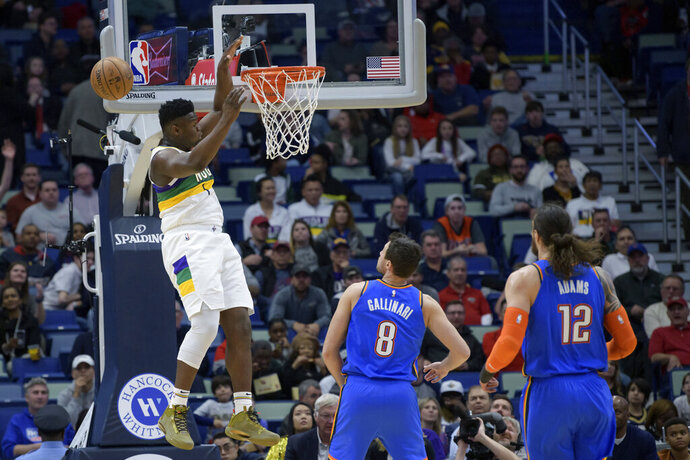 New Orleans Pelicans forward Zion Williamson (1) can't grab a pass at the basket, next to Oklahoma City Thunder forward Danilo Gallinari (8) during the first half of an NBA basketball game in New Orleans, Thursday, Feb. 13, 2020. (AP Photo/Matthew Hinton)