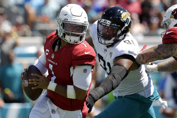 Arizona Cardinals quarterback Kyler Murray (1) scrambles way from Jacksonville Jaguars defensive end Dawuane Smoot (91) during the first half of an NFL football game, Sunday, Sept. 26, 2021, in Jacksonville, Fla. (AP Photo/Phelan M. Ebenhack)