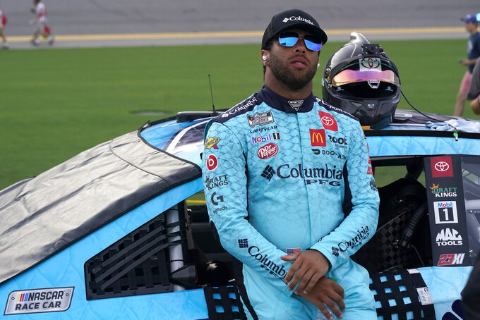 Bubba Wallace stands by his car before the NASCAR Cup Series auto race at Daytona International Speedway, Saturday, Aug. 28, 2021, in Daytona Beach, Fla. (AP Photo/John Raoux)