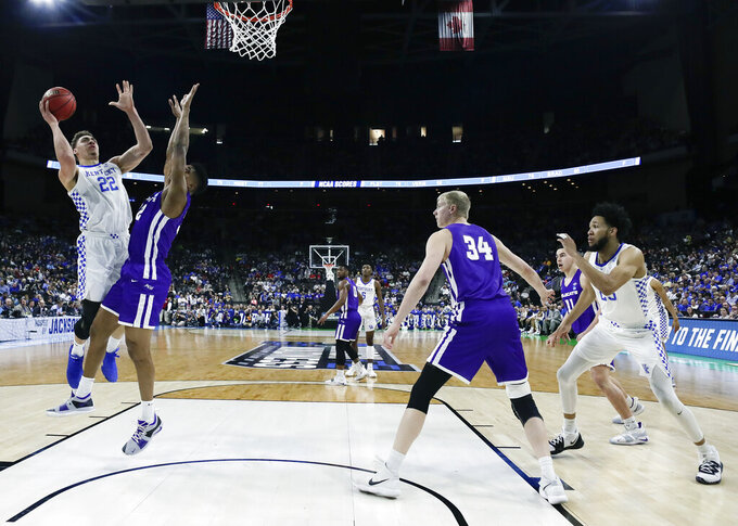 Kentucky's Reid Travis (22) shoots over Abilene Christian's Joe Pleasant as center Kolton Kohl (34) watches during the first half of a first-round game in the NCAA men's college basketball tournament in Jacksonville, Fla. Thursday, March 21, 2019. (AP Photo/John Raoux)