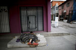 FILE - In this Wednesday, May 6, 2020 file photo, homeless women sleep outside on a mattress in the