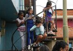 Girls watch an event for children at a soup kitchen in the Antimano neighborhood of Caracas, Venezuela, Tuesday, July 27,2021. The soup kitchen was celebrating a belated national children's day with different cultural activities, amid the new coronavirus pandemic. (AP Photo/Ariana Cubillos)