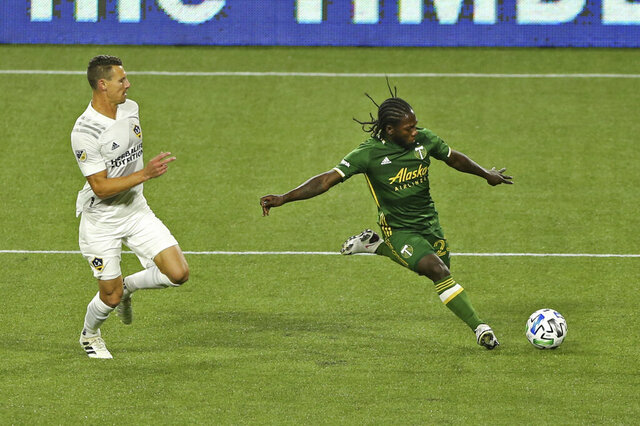 Portland Timbers' Yimmi Chara shoots on goal next to an LA Galaxy player during the first half of an MLS soccer match Wednesday, Oct. 28, 2020, in Portland, Ore. (Sean Meagher/The Oregonian via AP)