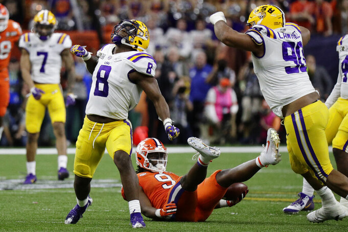 FILE - In this Jan. 13, 2020, file photo, LSU linebacker Patrick Queen celebrates after tackling Clemson running back Travis Etienne during the second half of the NCAA College Football Playoff national championship game in New Orleans. Queen was selected by the Baltimore Ravens during the first round of the NFL draft. (AP Photo/Sue Ogrocki, File)