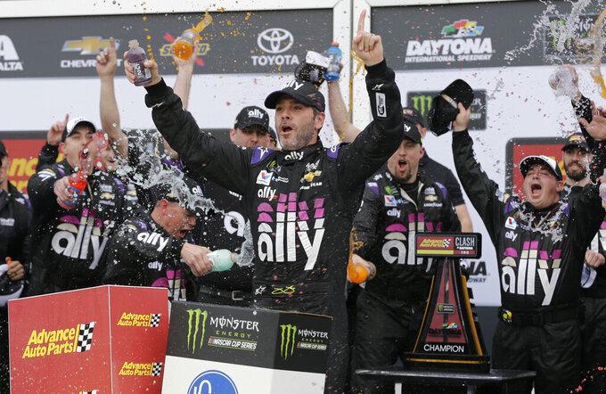 Jimmie Johnson, center, celebrates with his crew members after winning the NASCAR Clash auto race at Daytona International Speedway, Sunday, Feb. 10, 2019, in Daytona Beach, Fla. (AP Photo/Terry Renna)