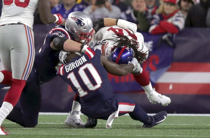 New York Giants linebacker Markus Golden, right, pulls free from New England Patriots center Ted Karras, left, and wide receiver Josh Gordon (10) after recovering a fumble in the first half of an NFL football game, Thursday, Oct. 10, 2019, in Foxborough, Mass. Golden scored a touchdown on the play. (AP Photo/Charles Krupa)