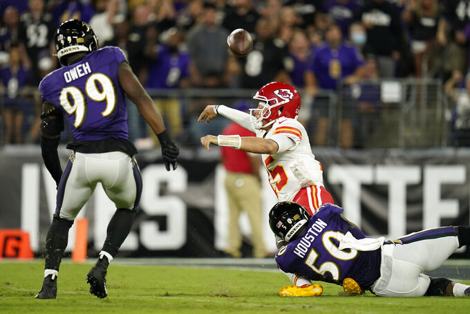 Kansas City Chiefs quarterback Patrick Mahomes, center, is pressured by Baltimore Ravens linebackers Justin Houston (50) and Odafe Oweh (99) in the first half of an NFL football game, Sunday, Sept. 19, 2021, in Baltimore. (AP Photo/Julio Cortez)