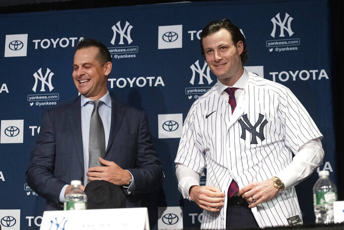 "FILE - In this Dec. 18, 2019, file photo, New York Yankees manager Aaron Boone, left, smiles as Gerrit Cole tries on a Yankee jersey as he is introduced in New York. The pitcher agreed to a 9-year $324 million contract. ""He's going to be a game changer for us,"" Yankees owner Hal Steinbrenner said. ""The city's buzzing, and it's continued since the day we signed him."" (AP Photo/Mark Lennihan, File)"