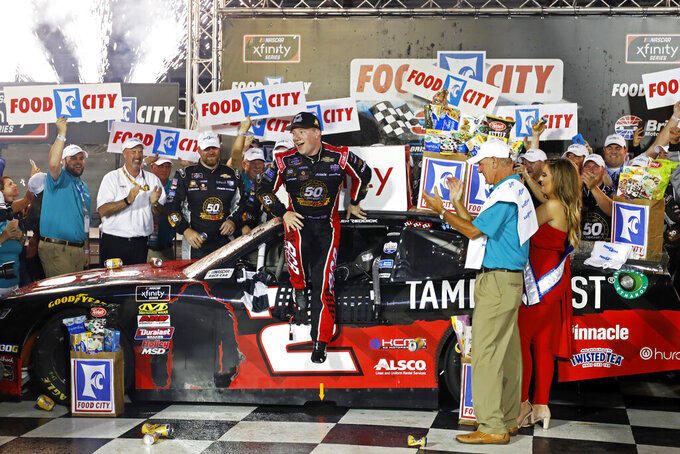 Tyler Reddick, center, leaps from his car after winning a NASCAR Xfinity Series auto race Friday, Aug. 16, 2019, in Bristol, Tenn. (AP Photo/Wade Payne)
