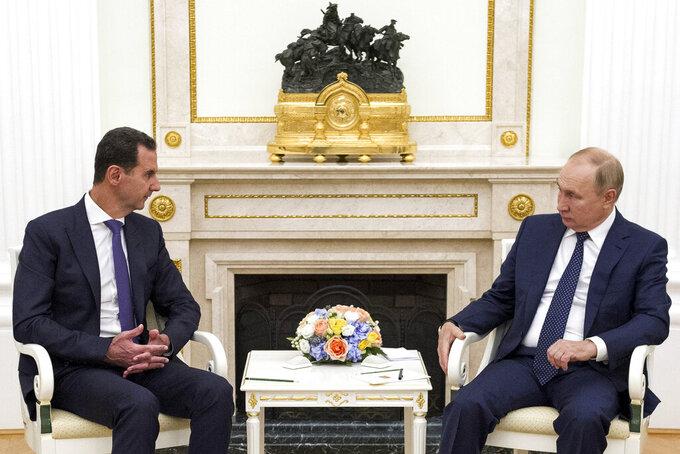 Russian President Vladimir Putin, right, listens to Syrian President Bashar Assad during their meeting in the Kremlin in Moscow, Russia, Monday, Sept. 13, 2021. (Mikhail Klimentyev, Sputnik, Kremlin Pool Photo via AP)