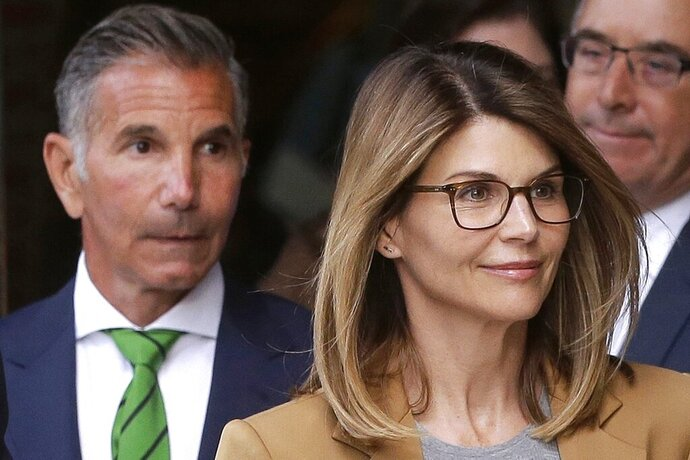 FILE - In this April 3, 2019, file photo, actress Lori Loughlin, front, and her husband, clothing designer Mossimo Giannulli, left, depart federal court in Boston after a hearing in a nationwide college admissions bribery scandal. In a court filing on Monday, July 13, 2020, lawyers for the couple, who admitted to paying $500,000 to get their daughters into the University of Southern California as fake crew recruits, asked a judge to lower their bail from $1 million to $100,000, saying they will not flee ahead of their August sentencing in the college admissions bribery case. (AP Photo/Steven Senne, File)