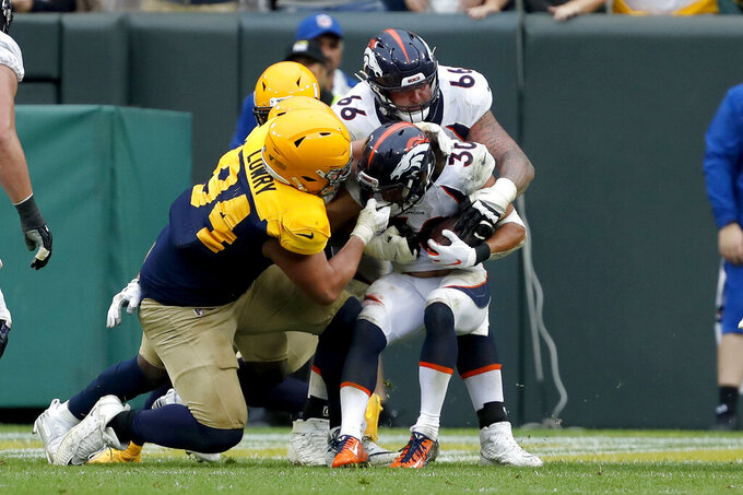 Denver Broncos running back Phillip Lindsay (30) fights his way past Green Bay Packers defensive end Dean Lowry (94) for a touchdown with the help of teammate offensive tackle Dalton Risner during the second half of an NFL football game Sunday, Sept. 22, 2019, in Green Bay, Wis. (AP Photo/Matt Ludtke)