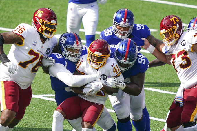 New York Giants' Leonard Williams (99) and Dalvin Tomlinson (94) tackle Washington Football Team's J.D. McKissic (41) during the first half of an NFL football game Sunday, Oct. 18, 2020, in East Rutherford, N.J. (AP Photo/John Minchillo)