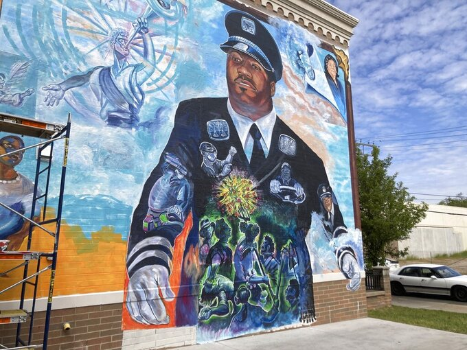 """A large mural honoring firefighter Capt. Franklin Williams and other Detroit public employees who died from COVID-19 is displayed on the side of a building, Monday, May 31, 2021, in Detroit. The mural, which faces a Detroit fire station, was created by artist Charles """"Chazz"""" Miller with assistance from students at University of Detroit Mercy, the Detroit Free Press reported. It was unveiled Sunday, May 30.   (AP Photo/Ed White)"""