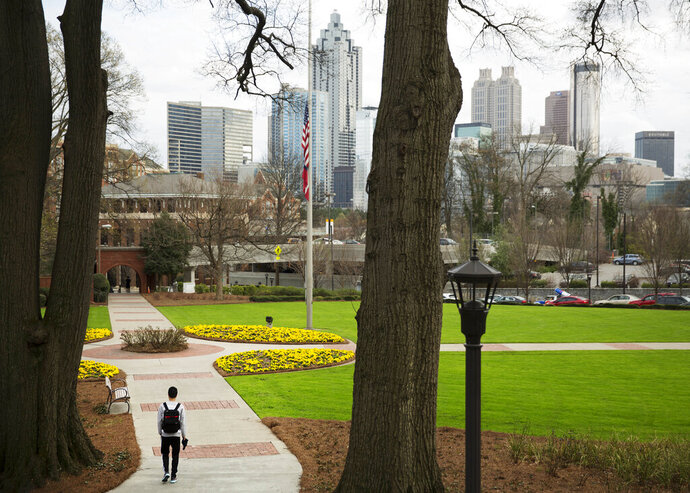 FILE - In this March 11, 2016, file photo, a pedestrian walks through the Georgia Tech campus as the downtown Atlanta skyline looms in the background. Enrollment at Georgia's public colleges and universities reached an all-time high for the fifth year in a row, powered mostly by increases at a few of the state's largest schools, the University System of Georgia reported Tuesday, Nov. 12, 2019. (AP Photo/David Goldman, File)
