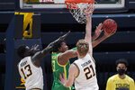 Oregon forward Chandler Lawson, center, shoots between California forwards Kuany Kuany (13) and Lars Thiemann (21) during the second half of an NCAA college basketball game in Berkeley, Calif., Saturday, Feb. 27, 2021. (AP Photo/Jeff Chiu)