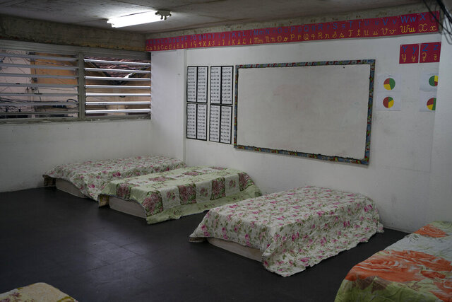Beds sit inside a classroom of a primary school inside the Sambadrome, repurposed as a shelter to house the homeless amid the spread of the new coronavirus in Rio de Janeiro, Brazil, Monday, March 30, 2020. (AP Photo/Leo Correa)