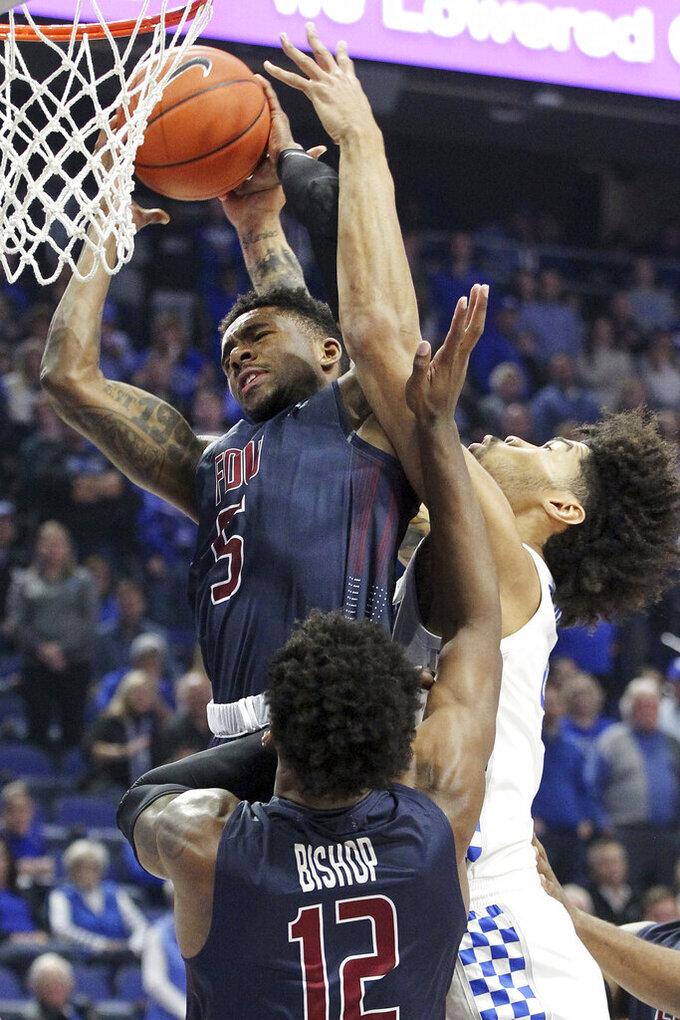Fairleigh Dickinson's Xzavier Malone-Key (5) pulls down a rebound near Kentucky's Nick Richards during the first half of an NCAA college basketball game in Lexington, Ky., Saturday, Dec. 7, 2019. (AP Photo/James Crisp)