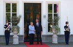 Dutch Prime Minister Mark Rutte, right, poses with German Chancellor Angela Merkel, at the entrance to his official residence in The Hague, Netherlands, Thursday Aug. 22, 2019.  Merkel and key Cabinet ministers are meeting their Dutch counterparts Thursday to discuss ways of tackling climate change together, as Germany is set to miss its emissions goals for 2020 by a wide margin.(AP Photo/Mike Corder)
