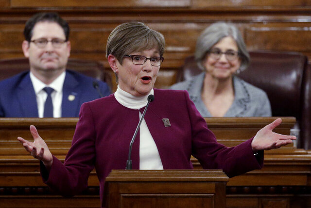 Flanked by Speaker of the House Ron Ryckman, left, and Senate President Susan Wagle, Gov. Laura Kelly outlines her agenda for the Republican-controlled Kansas Legislature in the annual State of the State address Wednesday, Jan. 15, 2020, in Topeka, Kan. (AP Photo/Charlie Riedel)