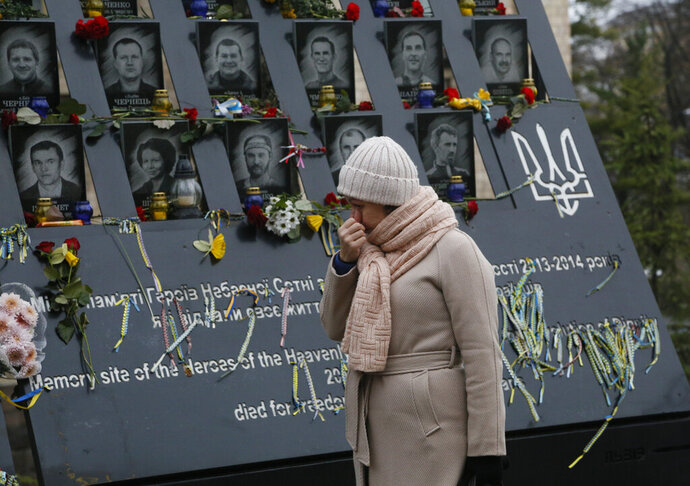 A woman pays her respect at a memorial dedicated to people died in clashes with security forces at the Independent Square (Maidan) in Kyiv, Ukraine, Thursday, Nov. 21, 2019 to mark the sixth anniversary of the beginning of the protests. People gather to commemorate the Maidan protest movement and the events which took place in late Feb. 2014 that led to the departure of former Ukrainian President Victor Yanukovich and the formation of a new government. (AP Photo/Efrem Lukatsky)