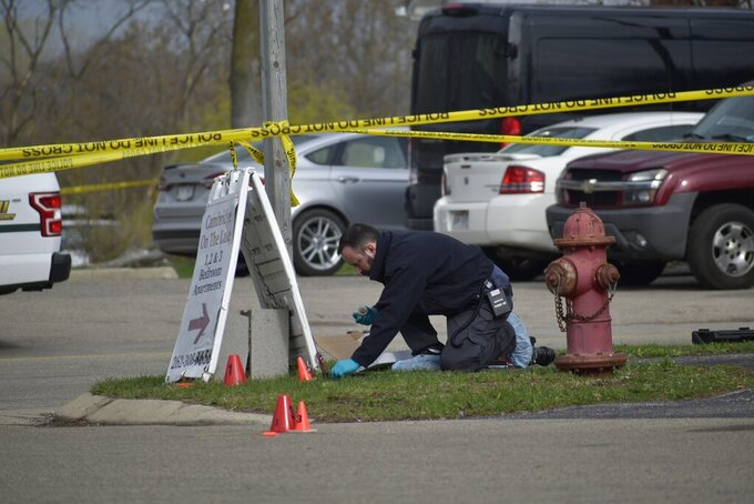 An investigator looks for evidence outside the Somers House Tavern in Somers, Wis., just outside of Kenosha, on Sunday, April 18, 2021, after a fatal shooting early Sunday morning. (Deneen Smith/The Kenosha News via AP)