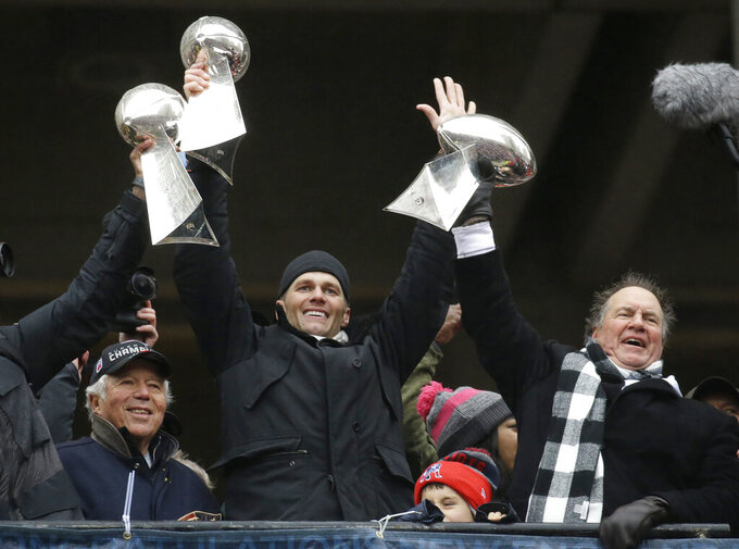 FILE - In this Feb. 7, 2017, file photo, New England Patriots quarterback Tom Brady holds up Super Bowl trophies along with head coach Bill Belichick, right, and team owner Robert Kraft, left, during a rally in Boston to celebrate the win over the Atlanta Falcons in the NFL Super Bowl 51 football game in Houston. Tom Brady is an NFL free agent for the first time in his career.  The 42-year-old quarterback with six Super Bowl rings  said Tuesday morning, March 17, 2020, that he is leaving the New England Patriots. (AP Photo/Elise Amendola, File)
