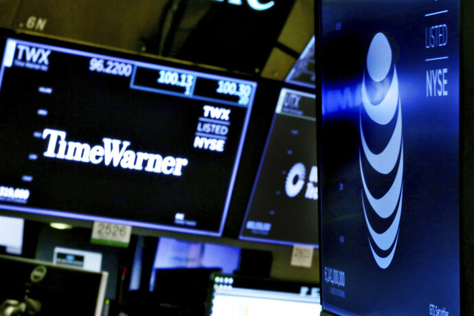 FILE - In this June 13, 2018, file photo, the logos for Time Warner and AT&T appear above alternate trading posts on the floor of the New York Stock Exchange. The Justice Department said in a one-sentence document Thursday, July 12, 2018, it is appealing the ruling last month by U.S. District Judge Richard Leon, which blessed one of the biggest media deals ever following a landmark antitrust trial. (AP Photo/Richard Drew, File)
