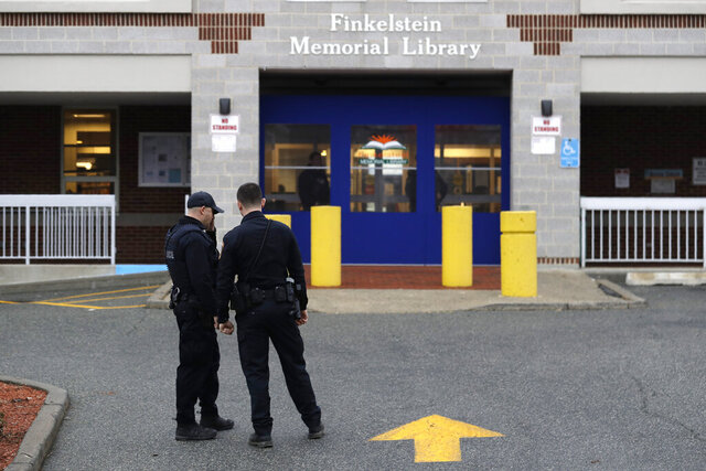 Policemen stand in front of the Finkelstein Memorial Library in Spring Valley, N.Y., Tuesday, Feb. 18, 2020. A female security guard was fatally stabbed on the third floor of the library Tuesday afternoon in a chaotic scene that ended when patrons gang-tackled the suspect until police could take him into custody, the Journal News reported.  (AP Photo/Seth Wenig)