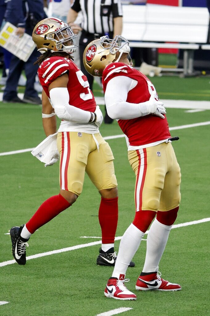 San Francisco 49ers' Arik Armstead, front, and Fred Warner (54) celebrate a Dallas Cowboys' Andy Dalton (14) sack by Armstead in the first half of an NFL football game in Arlington, Texas, Sunday, Dec. 20, 2020. (AP Photo/Michael Ainsworth)