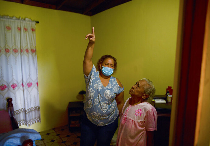 Maria Matilde Parrilla, 92, right, looks up as a municipal worker points a faulty joint in her wood and zinc roof, in Loiza, Puerto Rico, Thursday, May 28, 2020. Caribbean islands have rarely been so vulnerable as an unusually active hurricane season this year threatens a region still recovering from recent storms as it fights a worsening drought and a pandemic that has drained budgets and muddled preparations. (AP Photo/Carlos Giusti)