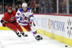 Carolina Hurricanes defenseman Joel Edmundson (6) chases New York Rangers left wing Brendan Lemieux (48) during the first period of an NHL hockey game in Raleigh, N.C., Thursday, Nov. 7, 2019. (AP Photo/Gerry Broome)