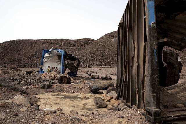 In this July 14, 2019 photo, 35-year-old Mohammed Eissa, an Ethiopian farmer and other migrants he met along the way, take shelter inside a damaged shipping container on the side of a highway, near Lac Assal, Djibouti. Over the past three years, the IOM reported 9,000 Ethiopians were deported each month. Many migrants have made the journey multiple times in what has become an unending loop of arrivals and deportations. Eissa is among them. This is his third trip to Saudi Arabia. (AP Photo/Nariman El-Mofty)