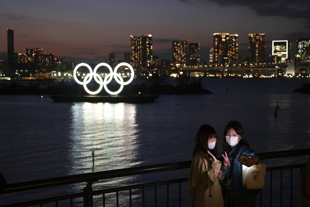 Two women take a selfie photo with the Olympic rings in the background in the Odaiba section of Tokyo, Thursday, March 12, 2020. The games were postponed due to the coronavirus pandemic. (AP Photo/Jae C. Hong)