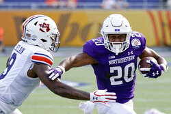 Northwestern running back Cam Porter (20) tries to get around Auburn linebacker Zakoby McClain, left, during the first half of the Citrus Bowl NCAA college football game, Friday, Jan. 1, 2021, in Orlando, Fla. (AP Photo/John Raoux)