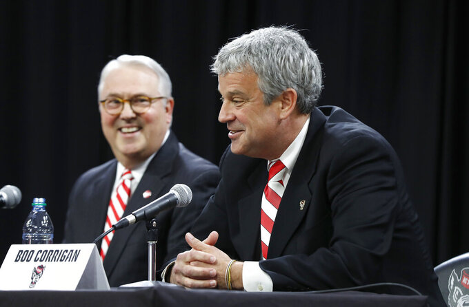 North Carolina State chancellor Randy Woodson, left, laughs with Boo Corrigan after Corrigan was introduced as N.C. State's new athletic director during a press conference at Reynolds Coliseum in Raleigh, N.C., Thursday, Jan. 31, 2019. (Ethan Hyman/The News & Observer via AP)