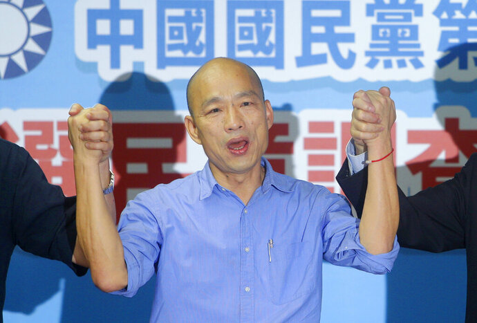 FILE - In this  July 15, 2019, file photo, Kaohsiung city mayor Han Kuo-yu and presidential candidate raises hands for the opposition of the Nationalist Party (KMT) for the upcoming presidential election in Taipei, Taiwan. Han has chosen a former Google executive and former state premier Cheng San-cheng as his running mate. Cheng received master's and doctoral degrees from Stanford and Cornell universities in the United States. (AP Photo/Chiang Ying-ying, File)