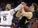 Iowa's Luka Garza (55) grabs a rebound ahead of Cincinnati's Cane Broome (15) in the first half during a first round men's college basketball game in the NCAA Tournament in Columbus, Ohio, Friday, March 22, 2019. (AP Photo/Tony Dejak)