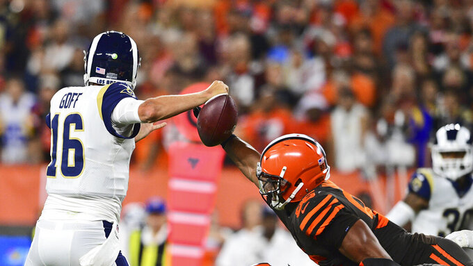 Cleveland Browns defensive end Myles Garrett, right, knocks the ball loose from Los Angeles Rams quarterback Jared Goff for a fumble during the first half of an NFL football game, Sunday, Sept. 22, 2019, in Cleveland. (AP Photo/David Dermer)