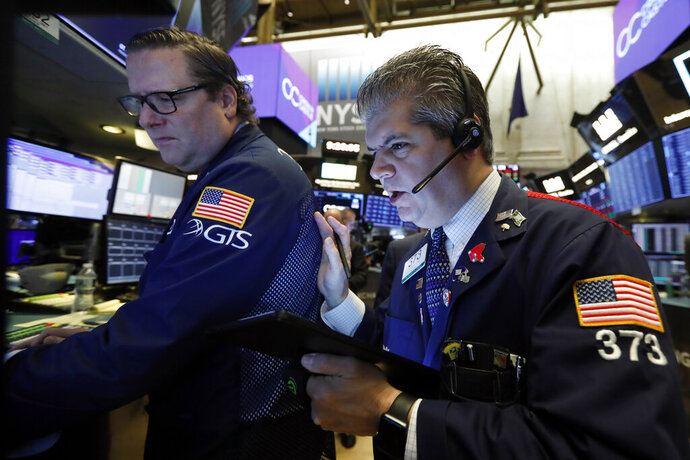 FILE - In this Tuesday, Oct. 29, 2019, file photo specialist Gregg Maloney, left, and trader John Panin work on the floor of the New York Stock Exchange. The U.S. stock market opens at 9:30 a.m. EDT on Friday, Nov. 1. (AP Photo/Richard Drew, File)