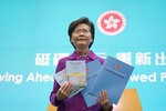 Hong Kong Chief Executive Carrie Lam poses with copies of her policy address at a news conference in Hong Kong, Wednesday, Nov. 25, 2020. Lam lauded the city's new national security law on Wednesday as