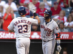 Houston Astros' Yuli Gurriel, right, celebrates Michael Brantley's two-run home run during the first inning of the team's baseball game against the Los Angeles Angels in Anaheim, Calif., Wednesday, July 17, 2019. (AP Photo/Kyusung Gong)