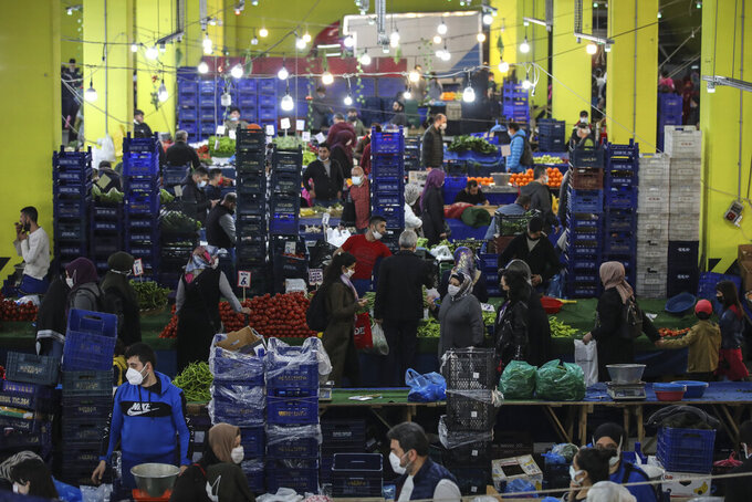 """People shop at the local market in Istanbul, Thursday, April 29, 2021, a few hours before the start of the latest lockdown to help protect from the spread of the coronavirus. People stocked up on groceries, shoppers filled markets and many left cities for their hometowns or the southern coast as Turkey's strictest COVID-19 lockdown yet came into effect late Thursday. President Recep Tayyip Erdogan imposed a """"full lockdown"""" until May 17 amid soaring COVID-19 infections and deaths. Turkey now ranks among the world's worst-hit countries and it's the first time that it is imposing a nearly three-week lockdown for the whole of the country. (AP Photo/Emrah Gurel)"""
