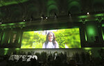 Climate activist Vanessa Nakate is seen on a giant screen as she speaks at the 'Austrian World Summit' at the Spanish Riding School in Vienna, Austria, Thursday, Sept. 17, 2020. (AP Photo/Ronald Zak)