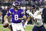 FILE - In this Dec. 30, 2018, file photo, Minnesota Vikings quarterback Kirk Cousins runs from Chicago Bears linebacker Isaiah Irving, right, during the second half of an NFL football game, in Minneapolis. Once again, Minnesota's biggest need in the draft is up front. The Vikings have used a first-round pick on an offensive lineman only once, in 2012, in the last 16 years, but they're due for an upgrade next week. (AP Photo/Bruce Kluckhohn, File)