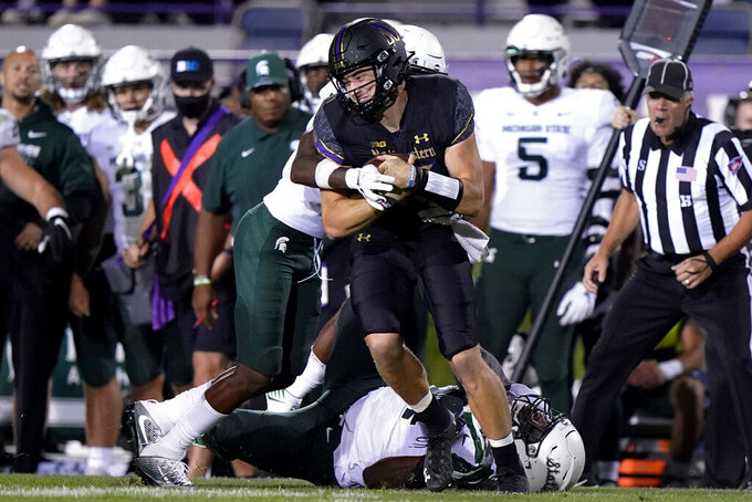 Northwestern quarterback Hunter Johnson (15) is tackled by Michigan State cornerback Marqui Lowery, left, and defensive tackle Dashaun Mallory during the second half of an NCAA college football game in Evanston, Ill., Friday, Sept. 3, 2021. Michigan State won 38-21. (AP Photo/Nam Y. Huh)